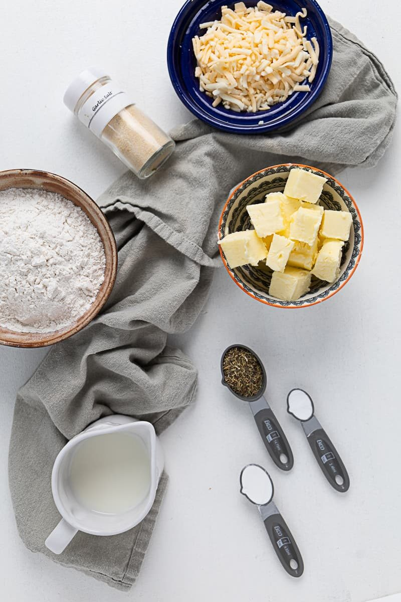 Top view of the ingredients in bowls and ramekins for cheese biscuit recipe