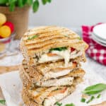 Stack of caprese chicken sandwich with basil in the back. Cheese is oozing out of the sandwich. .