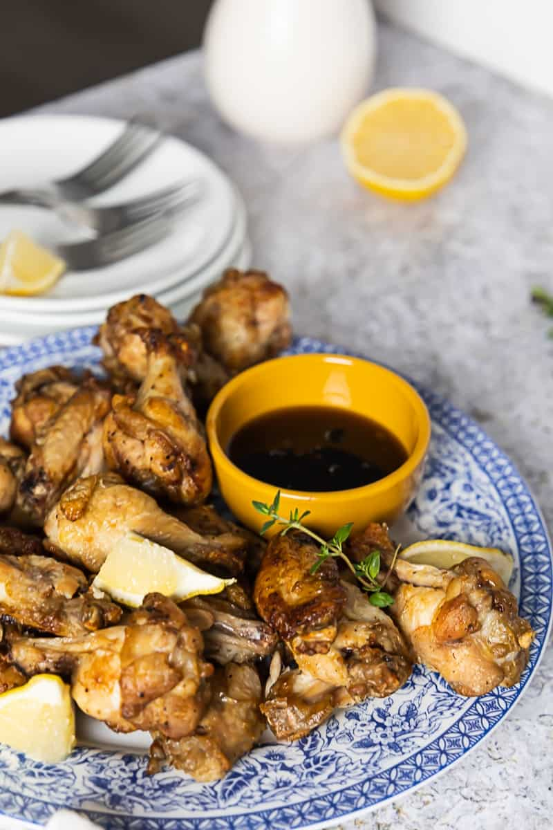 Side view of a blue plate with air fryer lemon pepper wings and a yellow mini bowl with sauce.