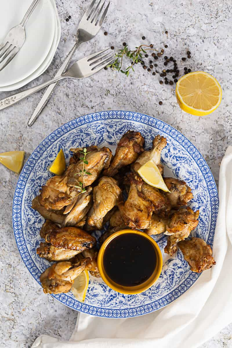 Top view of a blue plate with air fryer lemon pepper wings and fresh lemon on the side and grains of pepper