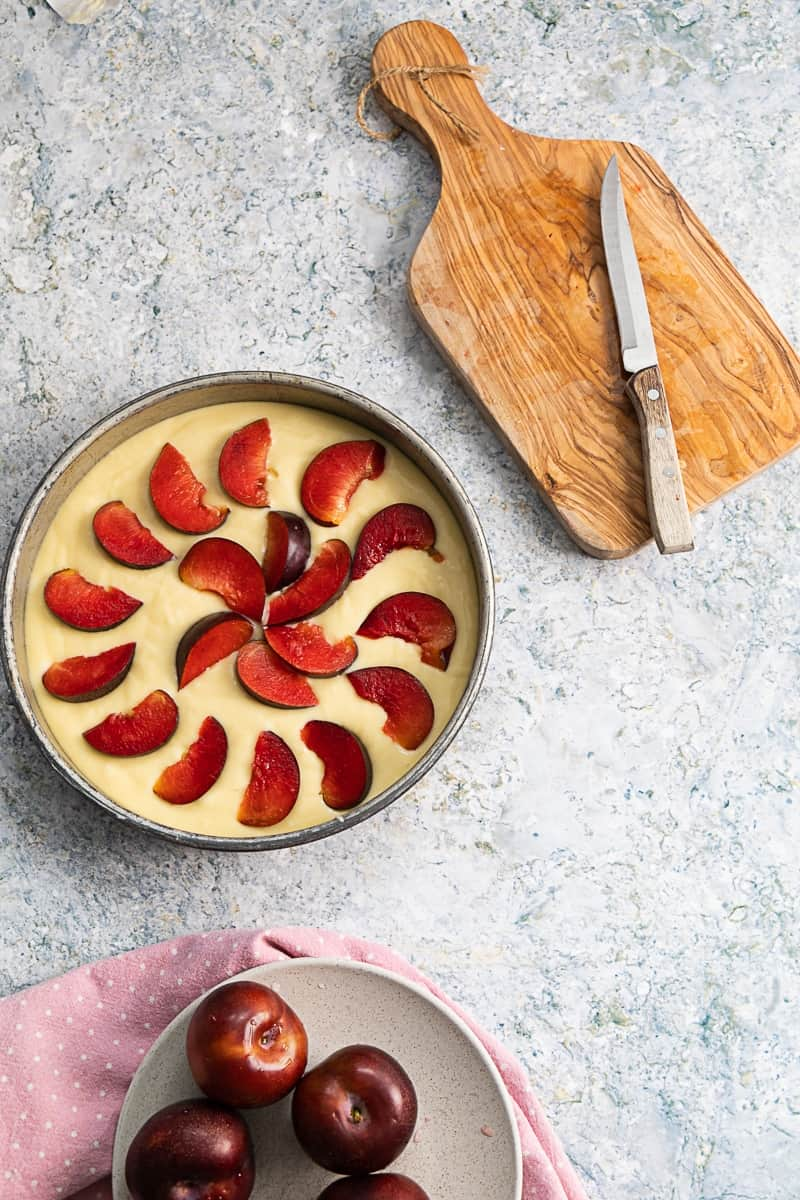 top view of uncooked yogurt plum cake with fresh plums on the side