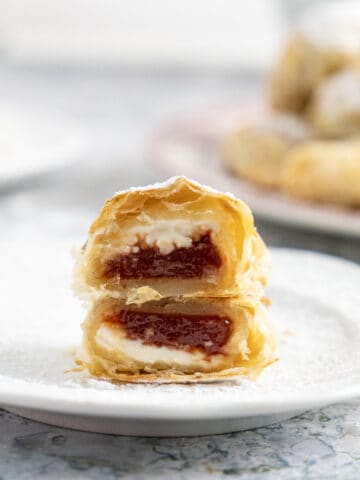 Side view of a sliced pastelitos de guayaba showing the cream cheese and the guava paste