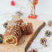 Chocolate Yule log on a a piece of wood. Pine cones around and a nutcracker in the back.